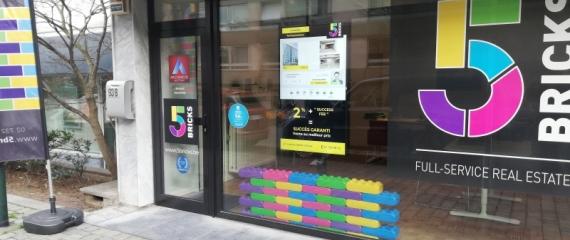Ecran vitrine d'affichage dynamique pour diffusion de biens immobiliers au sein de l'agence 5Bricks à Bruxelles