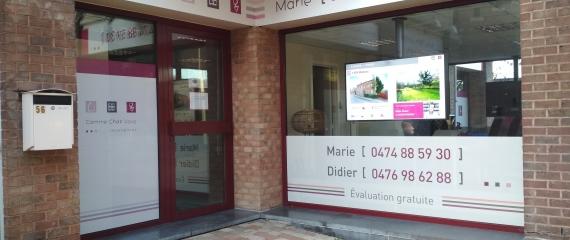 Deux écrans en vitrine d'une agence immobilière à Louvain-la-Neuve